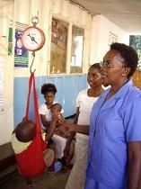 コンテナを改造した簡易クリニックで、保健推進員と一緒に赤ちゃんの体重を測る若いお母さん