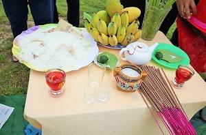 儀式の準備。お供えの果物、お皿に盛ったお米と紙幣(左上)、線香(右手前)など。