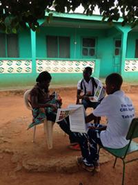 地域保健ボランティアによる家庭訪問。フリップチャートを使って説明中
