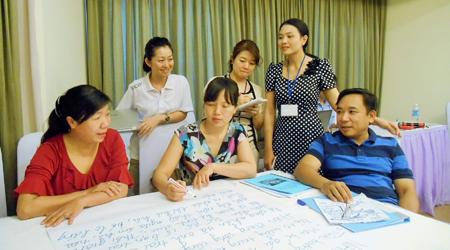 グループワークの結果をまとめる参加者と、日本助産師会の派遣専門家(山城五月氏、後列中央)ジョイセフの天池なほみプロジェクト・マネージャー(後列左)