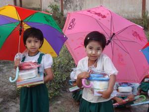 支援物資の弁当箱や傘を抱える子どもたち